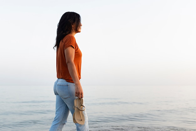 Side view of pensive woman taking a walk on the beach Free Photo