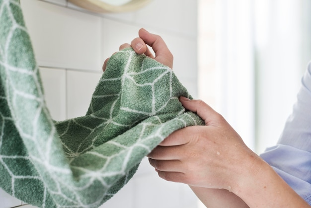Side view of person drying hands using towel Free Photo