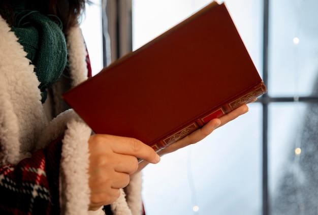 Persona di vista laterale che tiene un libro aperto Foto Gratuite