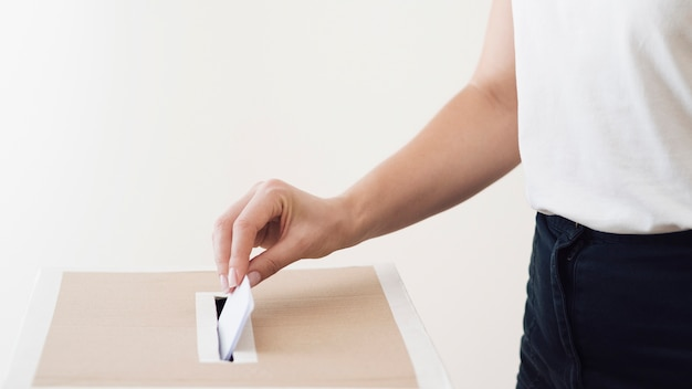 Side view person placing ballot in election box Free Photo