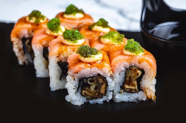Rotolo di philadelphia di vista laterale con il pesce fritto della salsa di color salmone e il caviale di tobiko sulla cima Foto Gratuite