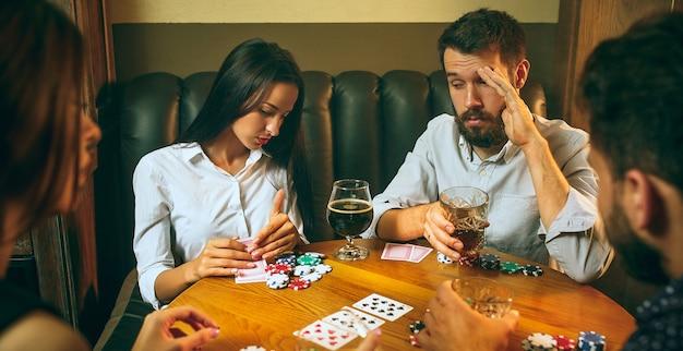 Foto di vista laterale di amici seduti al tavolo di legno. amici che si divertono durante il gioco da tavolo. Foto Gratuite
