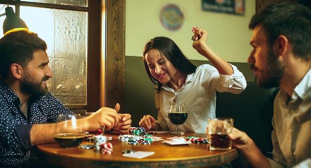 Foto di vista laterale di amici seduti al tavolo di legno. Foto Gratuite