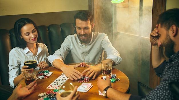 Foto di vista laterale di amici maschi e femmine seduti al tavolo di legno. uomini e donne che giocano a carte. mani con il primo piano dell'alcool. Foto Gratuite