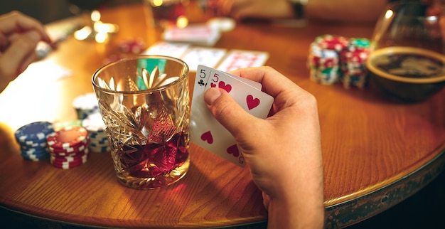 Side view photo of male and female friends sitting at wooden table. men and women playing card game. hands with alcohol close-up. Free Photo