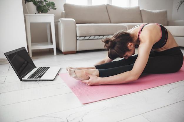 Фотография кавказской женщины, занимающейся йогой на полу и использующей ноутбук во время растяжки, вид сбоку Premium Фотографии