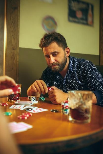 木製のテーブルに座っている友人の側面写真。ボードゲームで遊んでいる友人。 無料写真