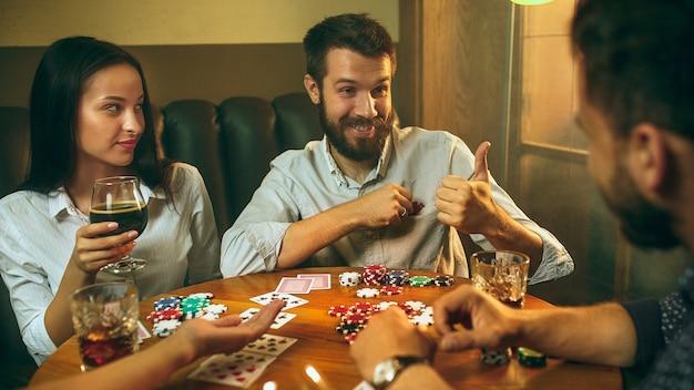 Фото вид сбоку друзей, сидящих за деревянным столом. друзья весело играют в настольную игру. Бесплатные Фотографии