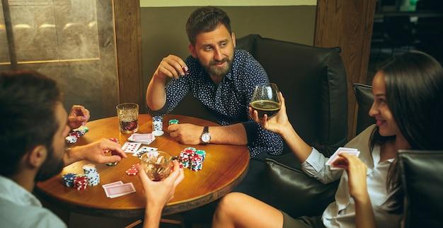 Фото взгляда со стороны друзей сидя на деревянном столе. друзья веселятся во время игры в настольную игру. Бесплатные Фотографии