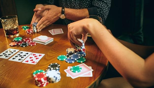 木製のテーブルに座っている男性と女性の友人の側面写真。男性と女性のトランプゲーム。アルコールのクローズアップと手。 無料写真