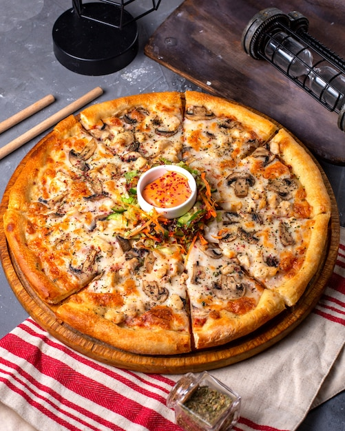 Side view of pizza with chicken and mushrooms served with sauce and vegetables salad on wooden plate Free Photo