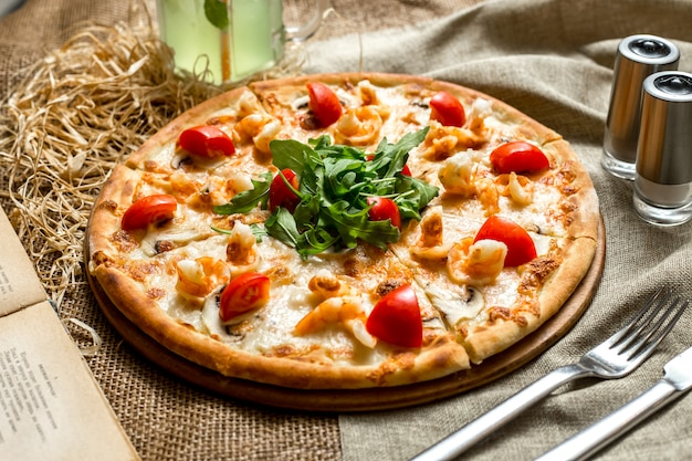Side view pizza with shrimp and mushrooms tomatoes and arugula and with a soft drink Free Photo