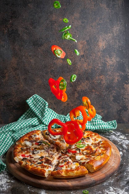 Side view pizza with slices of bell pepper and pizza slices in board cookware Free Photo