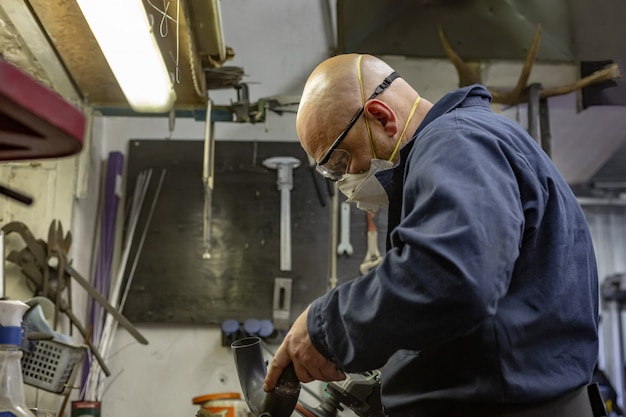 Side view portrait of man working in garage repairing motorcycle and customizing it Premium Photo