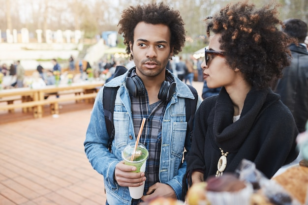 Side-view portrait of serious attractive dark-skinned boyfriend with afro hairstyle walking on food festival with girlfriend, drinking coffee and talking Free Photo