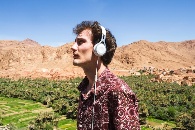 Side view portrait of young man listening to music in oasis Free Photo