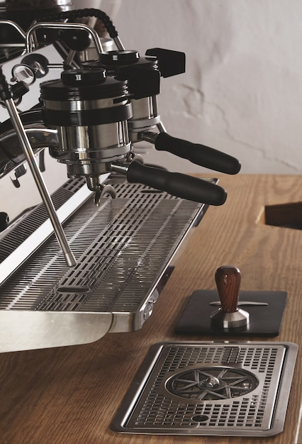 Вид сбоку профессиональная хромированная кофемашина с двумя головками и заряженными портафильтрами в кафе-магазине на деревянном толстом столе и тампер на кожаном падеспрессо, капучино, латте. Бесплатные Фотографии