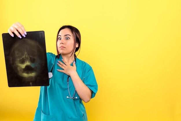Vista laterale del radiologo un radiologo è sorpreso dai raggi x del paziente Foto Gratuite
