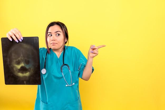 Vista laterale del radiologo un radiologo esamina i raggi x del paziente Foto Gratuite