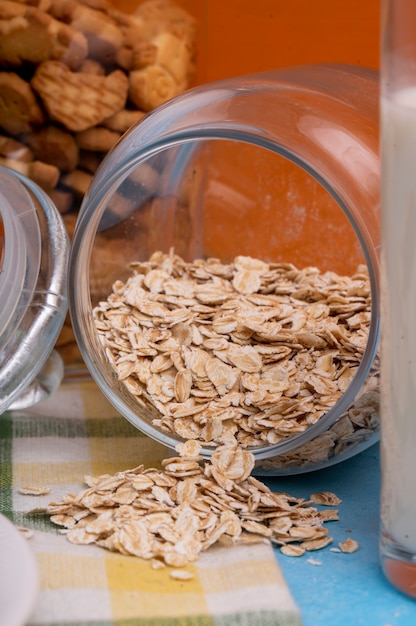 Side view of raw oatmeal flakes scattered from glass jar Free Photo