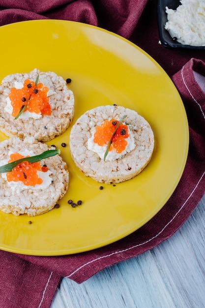 Vista laterale antipasto croccante di caviale rosso con ricotta tarhun di caviale rosso e pepe nero su un piatto Foto Gratuite