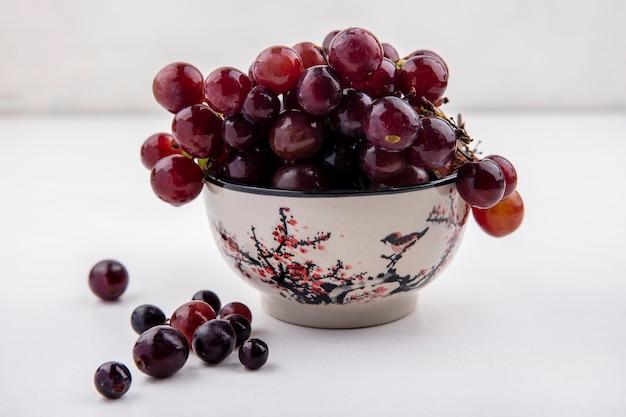 Vista laterale dell'uva rossa nella ciotola e su sfondo bianco Foto Gratuite