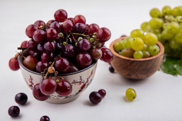 Vista laterale di uva rossa e acini d'uva bianca in ciotole con acini d'uva uva bianca e foglie su sfondo bianco Foto Gratuite