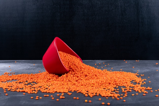 Side view red scattered lentils in red bowl on dark stone and black table Free Photo