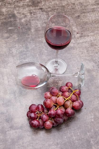 メガネとブドウの暗い石垂直の側面図赤ワイン 無料写真