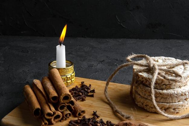 Vista laterale dei pani di riso legati con la corda e il bastoncino di cannella con una candela bruciante sul bordo di legno sul nero Foto Gratuite