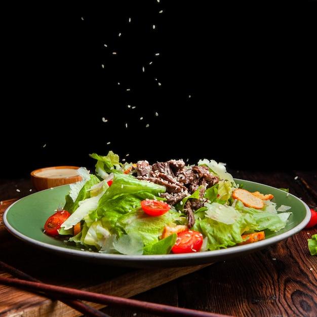 Riso di vista laterale che versa sul pasto delizioso dell'insalata in piatto con le bacchette su fondo di legno e nero. spazio per il testo Foto Gratuite