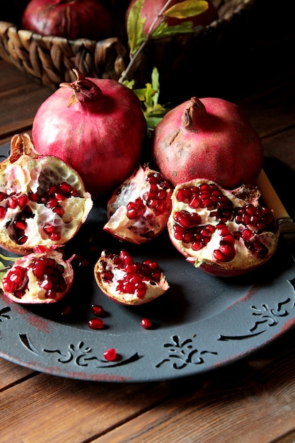 Side view ripe pomegranates with a branch from a tree Free Photo