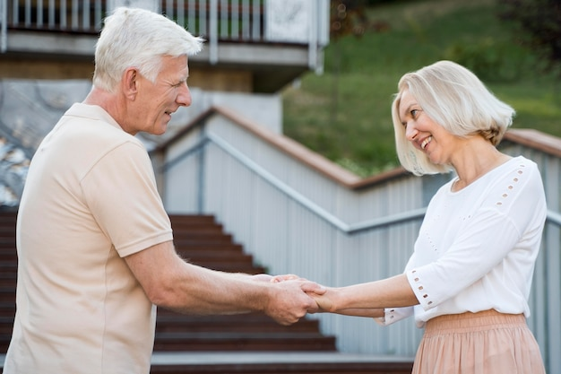Side view of romantic and loving senior couple holding hands outdoors Free Photo
