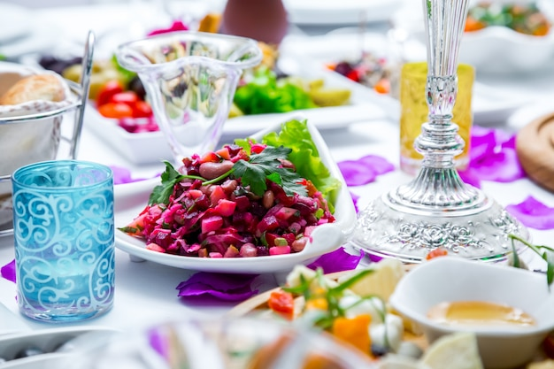 ガラスのパンとテーブルのスナックを添えたテーブルのサイドビューサラダヴィネグレット 無料写真