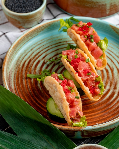 Side view of salmon tacos with red caviar and green onion on a plate Free Photo