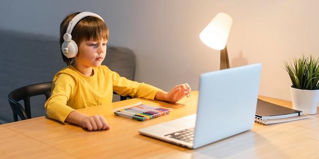 Scolaro di vista laterale in camicia gialla che prende lezioni virtuali Foto Gratuite