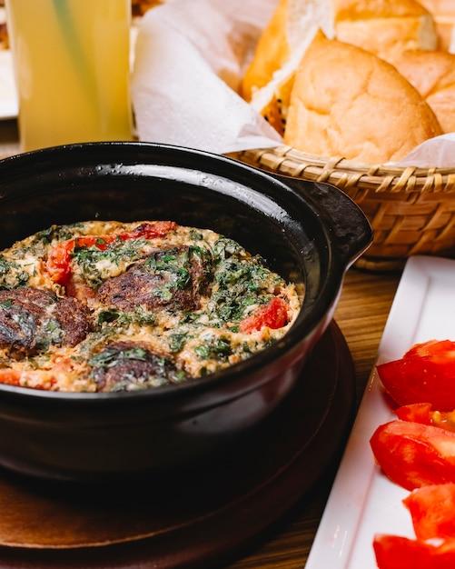 Вид сбоку яичница-болтунья с фрикадельками и зеленью в нарезанной сковороде ‹помидор и хлеб Бесплатные Фотографии
