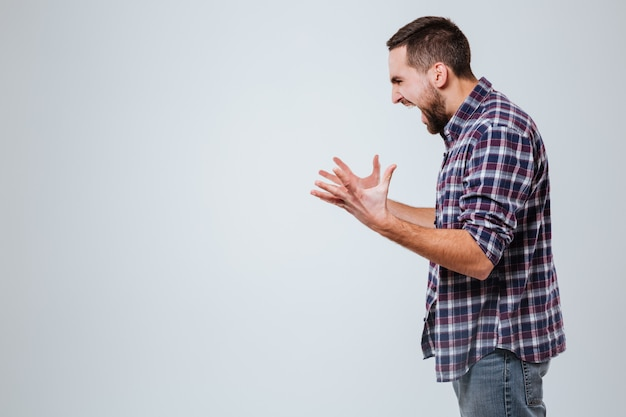 Side view of screaming bearded man in shirt Free Photo
