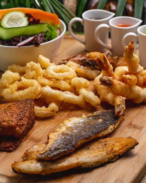 Antipasti di pesce vista laterale pesce gamberi calamari con salse e insalata Foto Gratuite