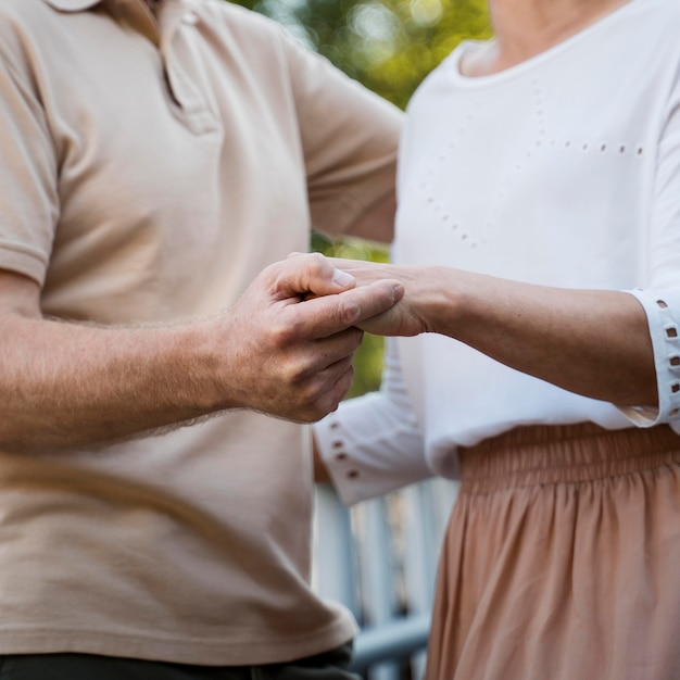 Side view of senior couple holding hands outdoors Free Photo