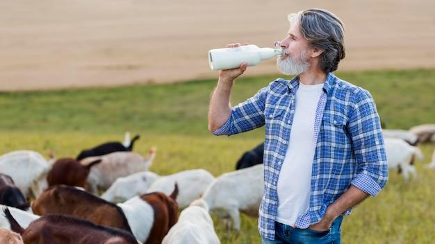 Вид сбоку старший пить козье молоко Бесплатные Фотографии