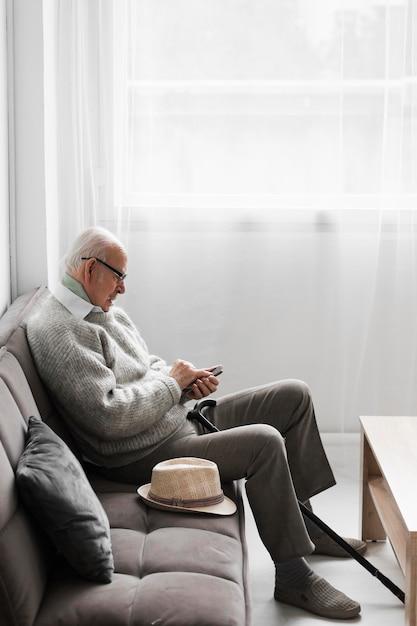 Vista laterale dell'uomo anziano in una casa di cura utilizzando lo smartphone Foto Gratuite