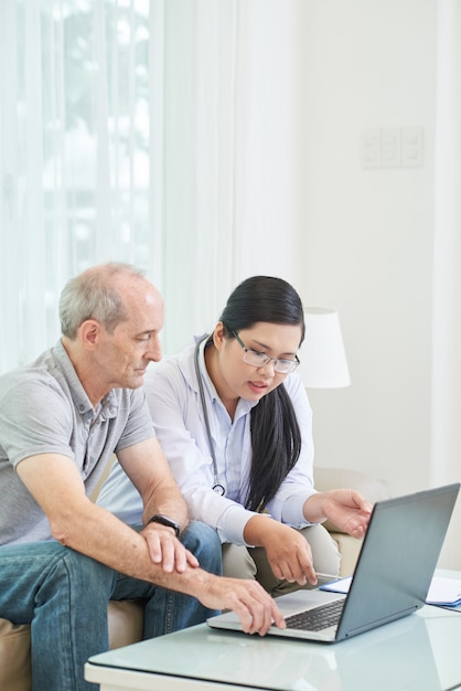 Side view of senior patient browsing the net on laptop with doctor Free Photo