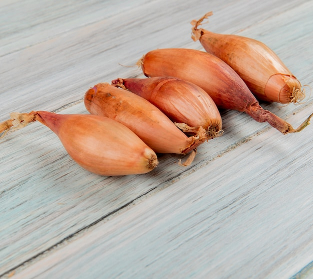 Side view of shallots on wooden background Free Photo