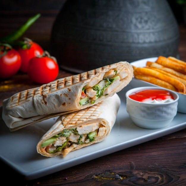 Side view shawarma pita roll with chicken and fried potatoes Free Photo