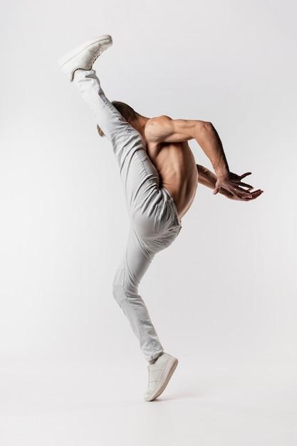 Vista laterale del ballerino maschio senza camicia in jeans e scarpe da ginnastica che posano con il vantaggio Foto Gratuite
