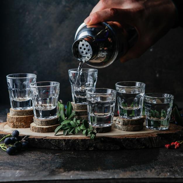 サイドビューショットグラス、ドリンク、バーテンダーがアルコールを注ぐ 無料写真
