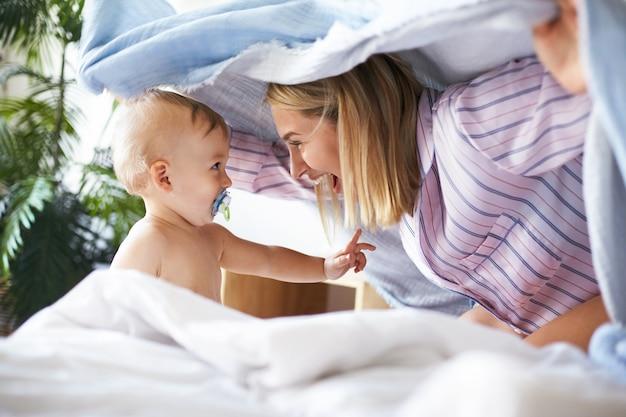Вид сбоку выстрел очаровательной радостной молодой женщины в пижаме, играющей в прятки с дочерью малыша. очаровательный милый младенец сосет соску, глядя на мать, с игривым выражением лица Бесплатные Фотографии