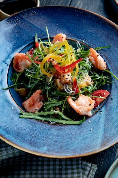 Vista laterale dell'insalata di gamberetti con peperoni e rucola su un piatto Foto Gratuite