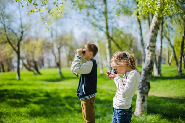 Side view of siblings with camera and binoculars Free Photo